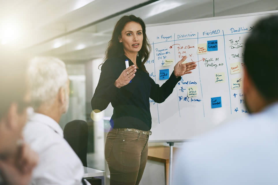 woman standing in front of whiteboard with students